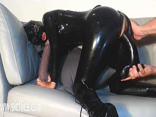 Rubber girl gets colossal strapon and fist in pussy